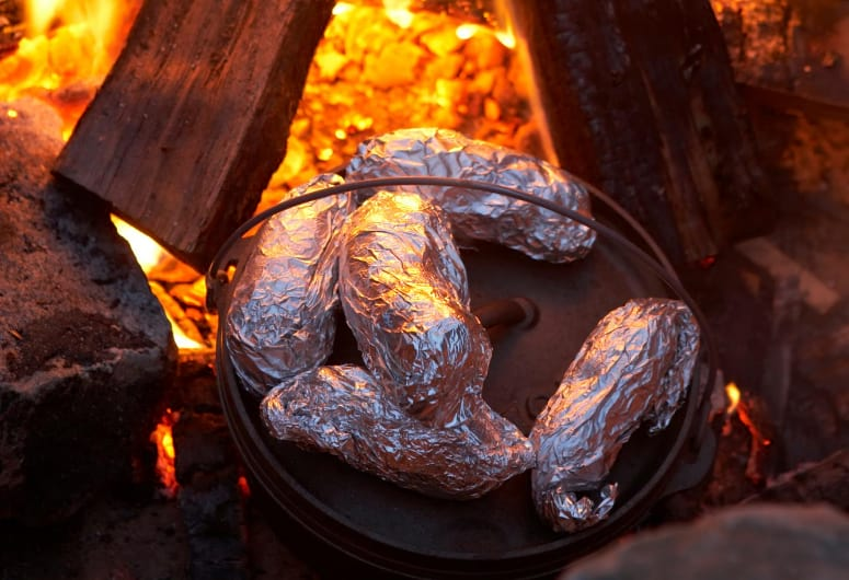 Foil packets next to a campfire