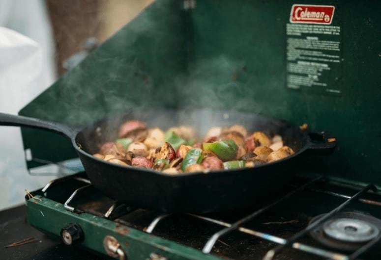 Spicy hash getting cooked on a Coleman stove