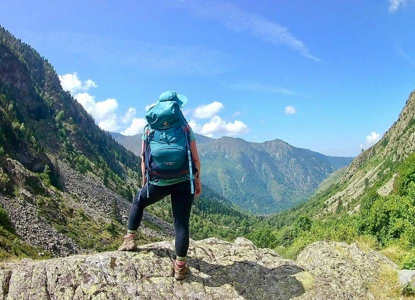 Woman wearing a blue backpack and black hiking leggings looking out across a valley