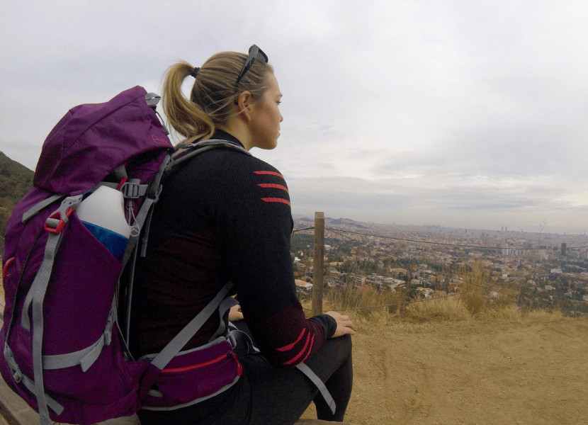 A woman wearing a purple hiking backpack sitting on a bench overlooking a city