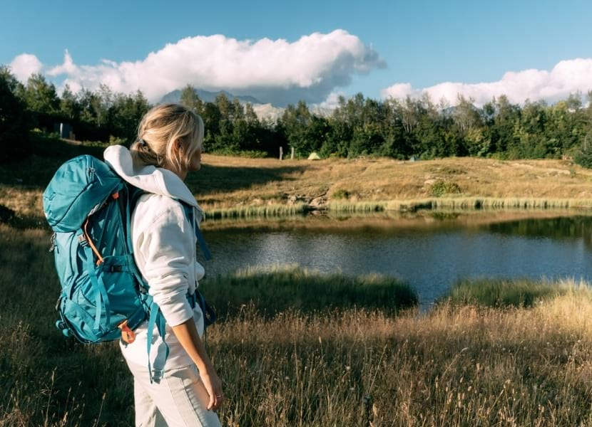 Woman wearing a blue hiking backpack and a white hoodie looking at a small lake