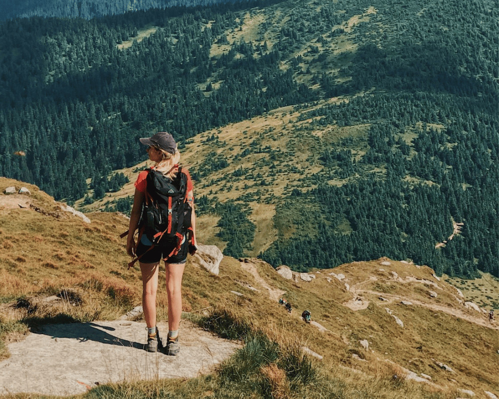 Woman wearing a baseball cap and a hiking backpack overlooking a valley