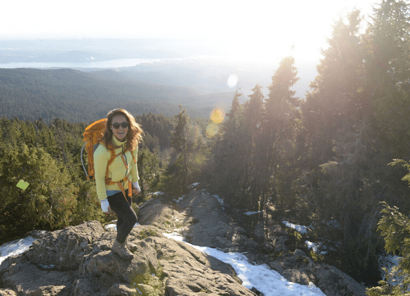 Woman standing on top of a mountain peak smiling (wearing sunglasses, a yellow jacket, black leggings, and an orange backpack)