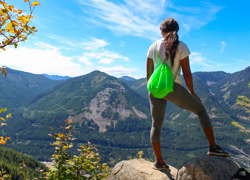 Woman standing on a rock looking over a valley with mountains in the background (wearing hiking leggings, a neon green backpack, and a white t shirt)