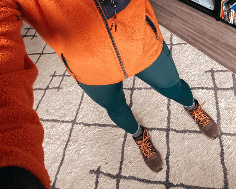 Cait wearing Arc'Teryx Oriel hiking leggings and an orange fleece jacket