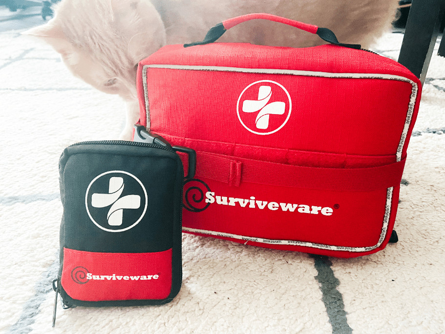 The Surviveware large kit with the included mini kit sitting next to it - there's also an orange cat sniffing the large kit