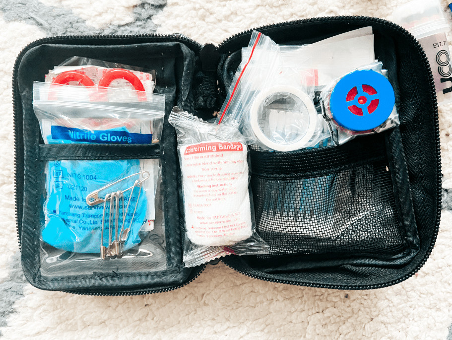 The inside of the mini kit - you can see a package of gloves, safety pins, a conforming bandage, a CPR kit, medical tape, q-tips, and a pair of shears